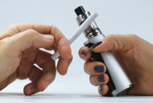 Addiction. A man's hand with a cigarette and a woman's hand holding an e-cigarette.